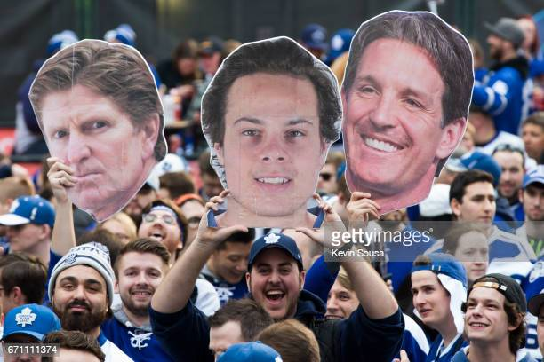 Fans hold up a photo of Mike Babcock head coach of the Toronto Maple Leafs Auston Matthews and Brendan Shanahan president of the Toronto Maple Leafs...
