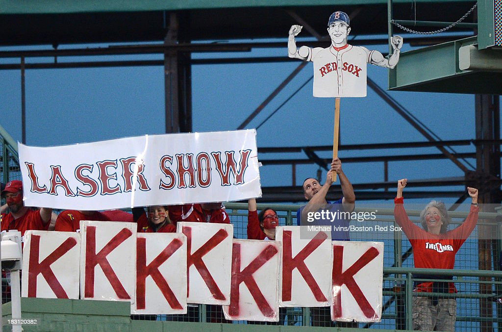 Fans hold up a sign in support of Dustin Pedroia #15 of the Boston Red Sox as he bats against the Tampa Bay Rays during the eighth inning of Game One of the American League Division Series on October 4, 2013 at Fenway Park in Boston, Massachusetts.