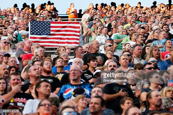 Fans hold up an American Flag in the grandstands during the NASCAR Sprint Cup Series IRWIN Tools Night Race at Bristol Motor Speedway on August 22...