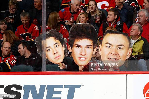 Fans hold up cardboard cutouts of Johnny Gaudreau Sean Monahan and Jiri Hudler of the Calgary Flames during the game against the Arizona Coyotes at...