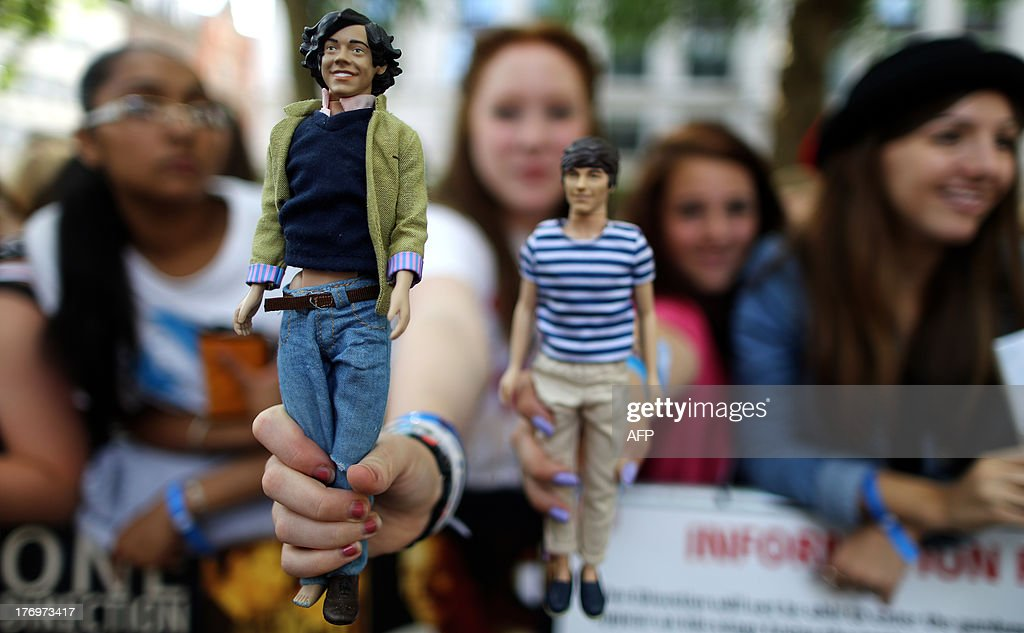Fans hold up dolls of the British boyband One Direction as their wait for their arrival ahead of the world premier of their feature film 'One Direction: This Is Us' in Leicester Square, central London, on August 20, 2013. The film, made by 'Super Size Me' director Morgan Spurlock, shows the group in concert at London's O2 Arena, along with fly-on-the-wall footage showing what life is like inside one of the world's biggest bands.