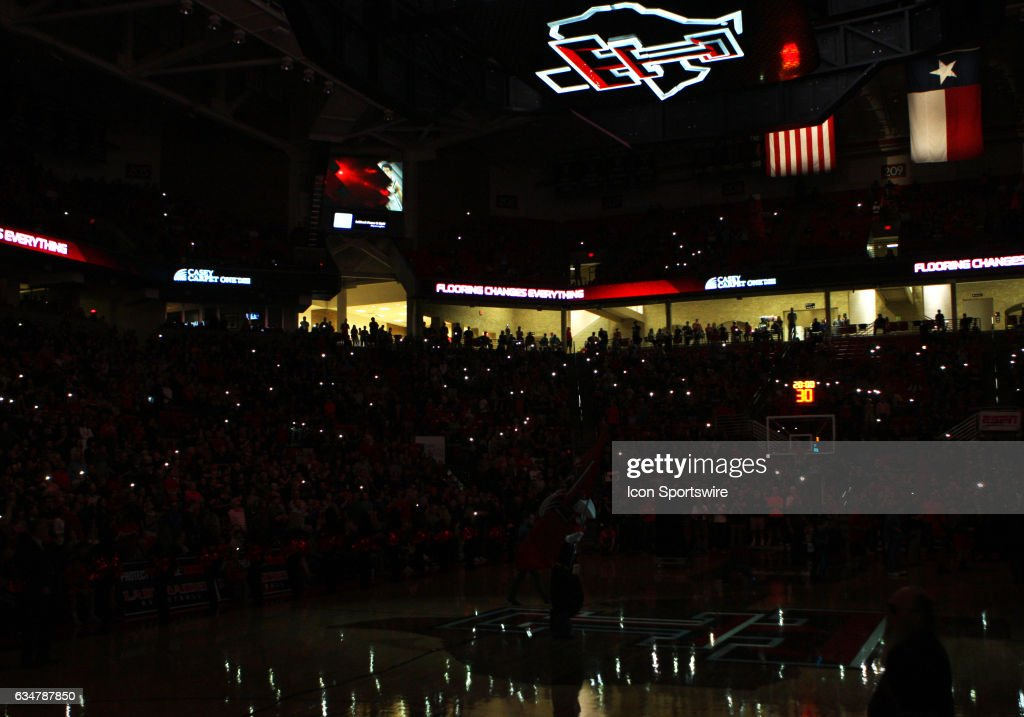 Fans hold up lights in the dimmed United Supermarkets Arena as the home starting lineup is announced before the start of the Texas Tech University Red Raider's home basketball game against the University of Kansas Jayhawks on February 11, 2017, in Lubbock, TX.
