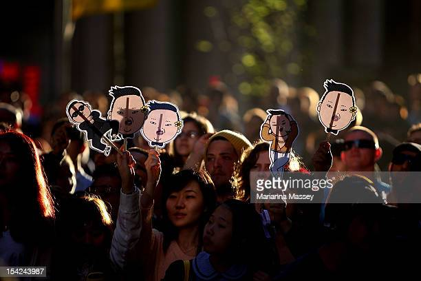 Fans hold up signs as South Korean rapper Psy performs live on Channel 7's 'Sunrise' at Martin Place on October 17 2012 in Sydney Australia