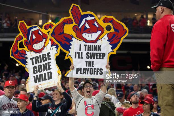 Fans hold up signs behind the Indians dugout as they celebrate following the 2017 American League Divisional Series Game 2 between the New York...