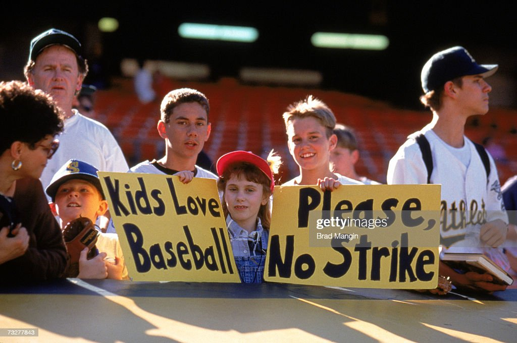 Fans hold up signs in protest of the baseball strike prior to the game between the Seattle Mariners and the Oakland Athletics at the Oakland Coliseum...