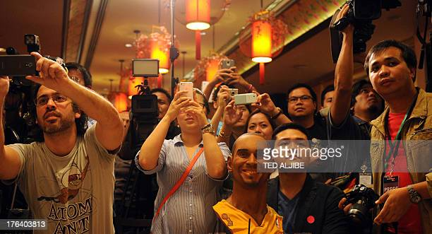 Fans hold up their mobile phones as they photograph fifteentime NBA AllStar basketball player Kobe Bryant while a bust of Bryant is seen among them...