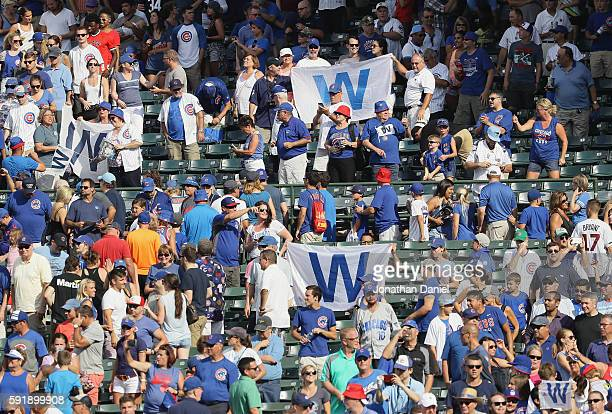 Fans hold W flags after the Chicago Cubs beat the Milwaukee Brewers at Wrigley Field on August 18 2016 in Chicago Illinois The Cubs defeated the...