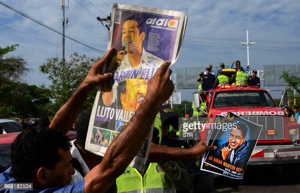 Fans holds banners with photos of Colombian singer Martin Elias during his funeral in Valledupar northern Colombia on April 16 2017 The...