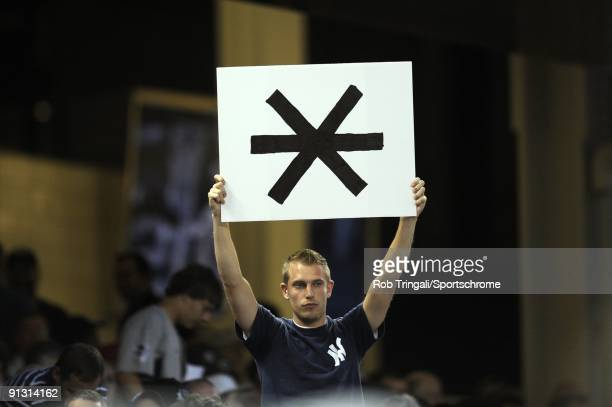 A fans holds up a asterisk sign in the crowd during the game between the Boston Red Sox and the New York Yankees at Yankee Stadium on August 6 2009...