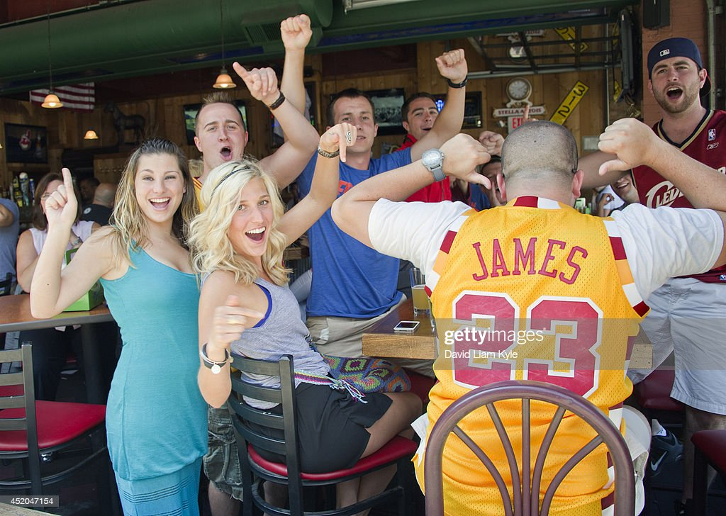 Fans in downtown Cleveland don their #23 LeBron James jerseys and celebrate shortly after he announced his return to the Cleveland Cavaliers on July 11, 2014 in Cleveland, Ohio.
