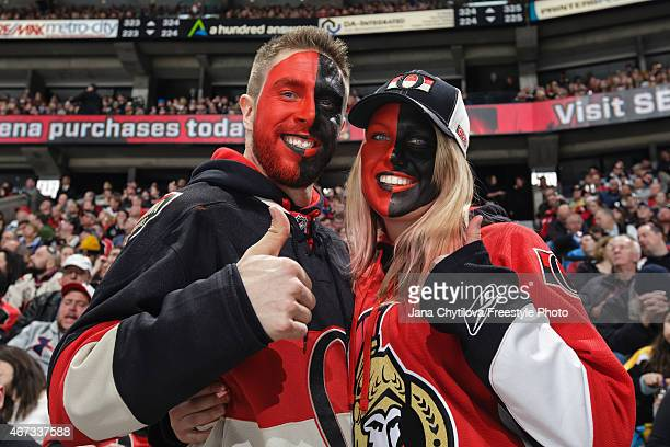 Fans in face paint ham it up during an NHL game between the Ottawa Senators and the Boston Bruins at Canadian Tire Centre on March 19 2015 in Ottawa...