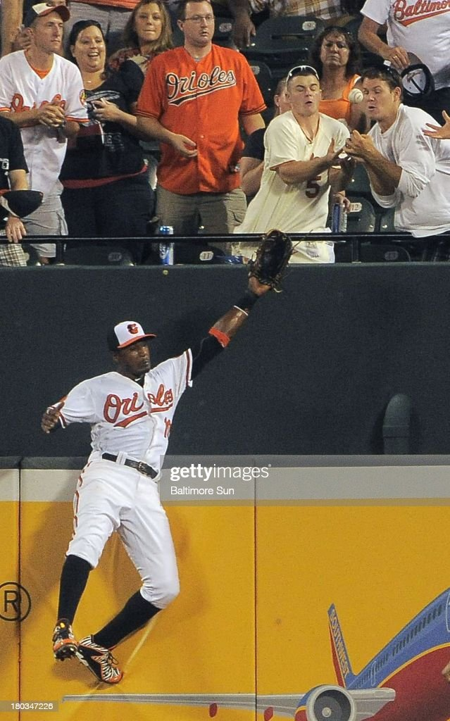 Fans in the bleachers catch a home run by the New York Yankees' Robinson Cano as Baltimore Orioles center fielder Adam Jones leaps in vain during the ninth inning at Oriole Park at Camden Yards on Wednesday, September 11, 2013, in Baltimore, Maryland. The Yankees won, 5-4.