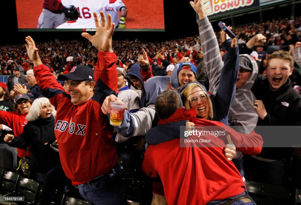 Fans in the bleachers celebrate David Ortiz's home run in the eighth inning to tie the game. The Boston Red Sox hosted the Detroit Tigers in Game Two of the American League Championship Series at Fenway Park.