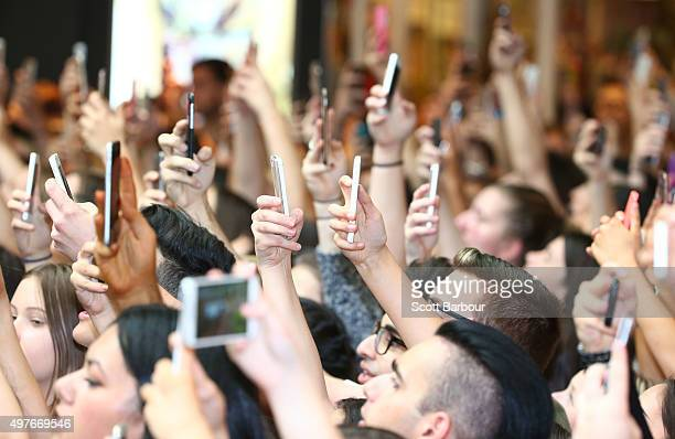 Fans in the crowd hold their mobile phones aloft as they wait for Kendall Jenner and Kylie Jenner to arrive at Chadstone Shopping Centre on November...