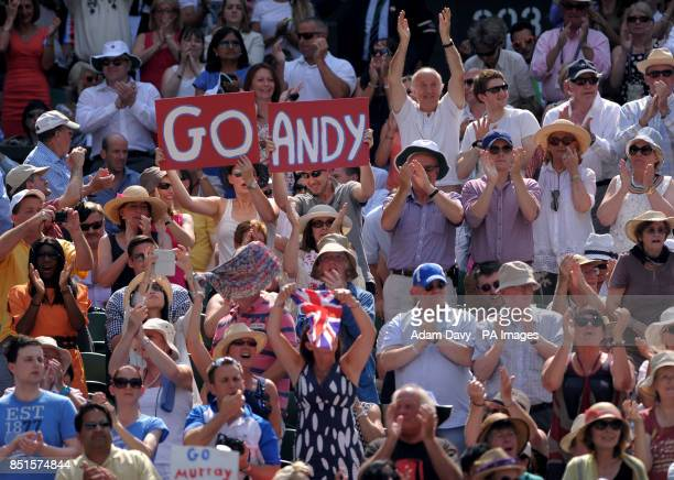 Fans in the crowd show their support for Great Britain's Andy Murray during his match against Serbia's Novak Djokovic on day thirteen of the...