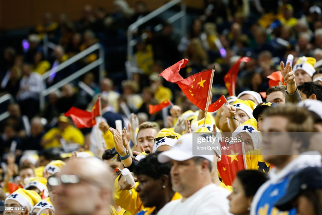 Fans in the Michigan student section wave flags of the People's Republic of China before the start of a regular season non-conference basketball game between the UCLA Bruins and the Michigan Wolverines on December 9, 2017 at the Crisler Center in Ann Arbor, Michigan. Michigan defeated UCLA 78-69 in overtime.