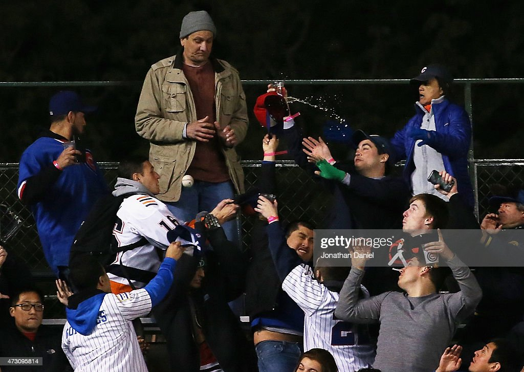 Fans in the new left field bleachers scramble to catch a home run ball hit by Kris Bryant of the Chicago Cubs in the 8th inning against the New York Mets at Wrigley Field on May 12, 2015 in Chicago, Illinois.