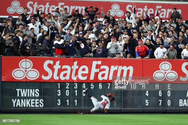 Fans in the outfield cheer as Eddie Rosario of the Minnesota Twins falls to the ground on Aaron Judge of the New York Yankees two run home run...
