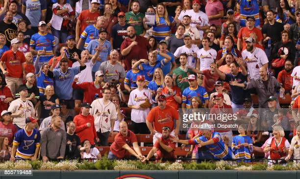 Fans in the outfield reach for solo home run ball hit by the St Louis Cardinals' Paul DeJong in the fourth inning against the Milwaukee Brewers on...
