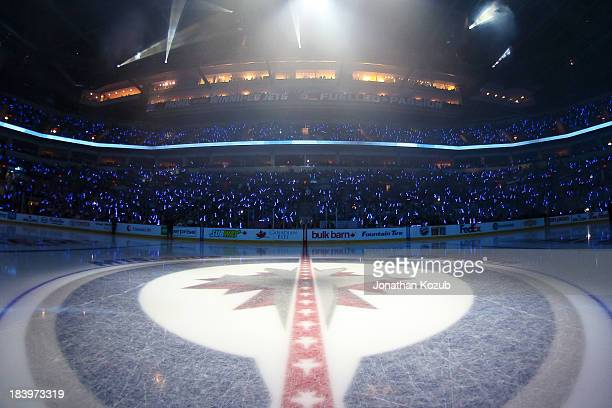 Fans in the stands help illuminate the arena with the use of 15004 glow sticks for the player introductions prior to NHL action between the Winnipeg...