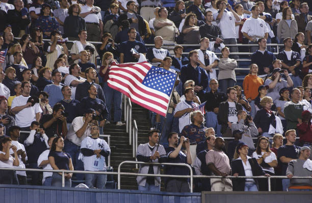 d1d0163ff0f Fans in the stands wave an American flag during the game between the New  York Yankees