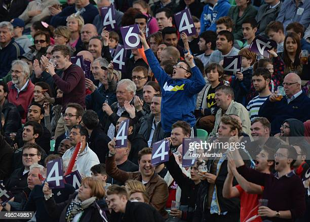 Fans indicate four runs scored during the NatWest T20 Blast match between Surrey and Middlesex Panthers at The Kia Oval on May 30 2014 in London...