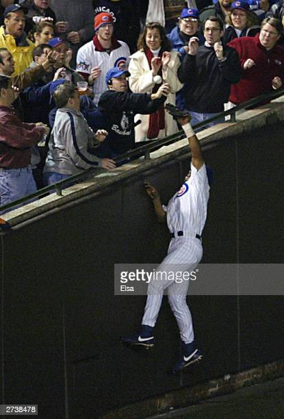Fans interfere with outfielder Moises Alou of the Chicago Cubs on a ball hit by Luis Castillo of the Florida Marlins in the eighth inning during Game...