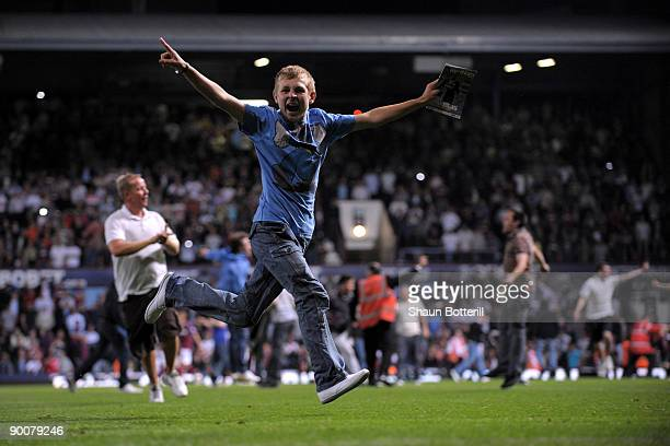 Fans invade the pitch during the Carling Cup second round match between West Ham United and Millwall at Upton Park on August 25 2009 in London...