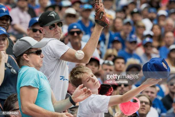 Fans jostle to try to catch a foul ball during the regular season MLB game between the Los Angeles Angels of Anaheim and the Toronto Blue Jays at...
