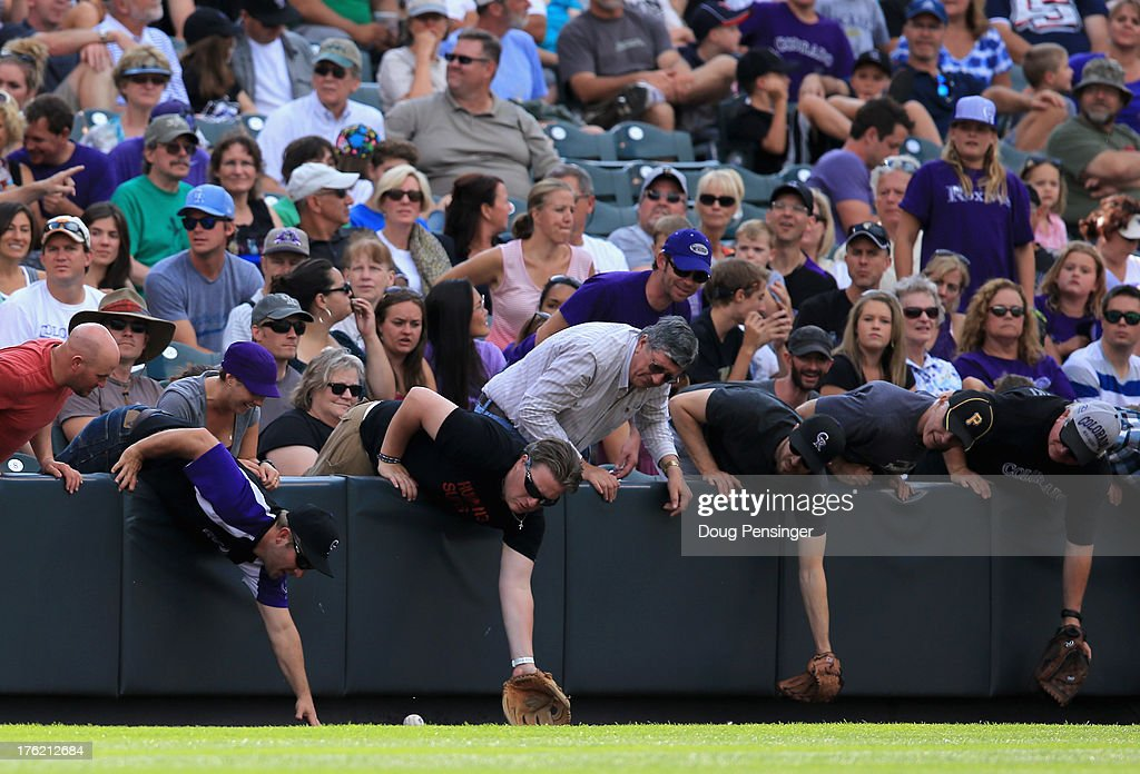 Fans lean over the wall in pursuit of a foul ball as the Pittsburgh Pirates face the Colorado Rockies at Coors Field on August 11, 2013 in Denver, Colorado. The Rockies defeated the Pirates 3-2 and swept the three game series.