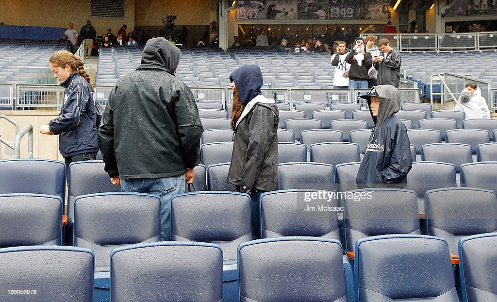 Fans leave after a game between the New York Yankees and the Toronto Blue Jays has been postponed due to rain at Yankee Stadium on May 19, 2013 in the Bronx borough of New York City.