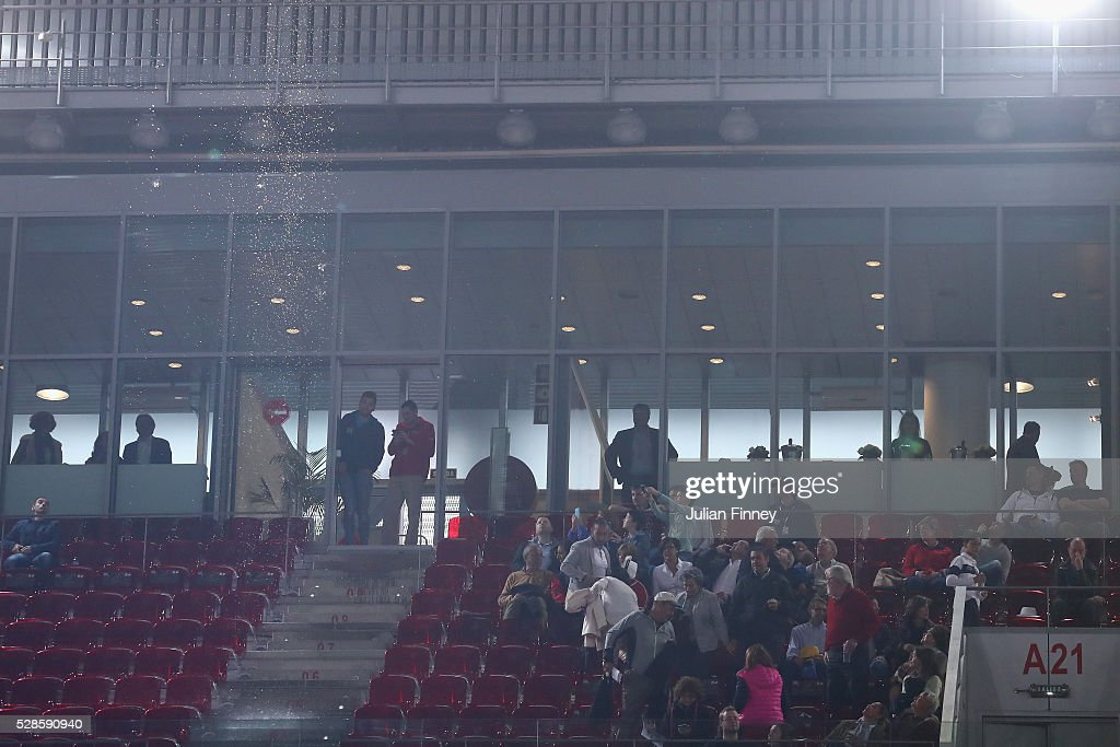 Fans leave their seats as rain falls through the roof on centre court as Dominika Cibulkova of Slovakia plays Louisa Chirico of USA in the semi finals during day seven of the Mutua Madrid Open tennis tournament at the Caja Magica on May 06, 2016 in Madrid, Spain.