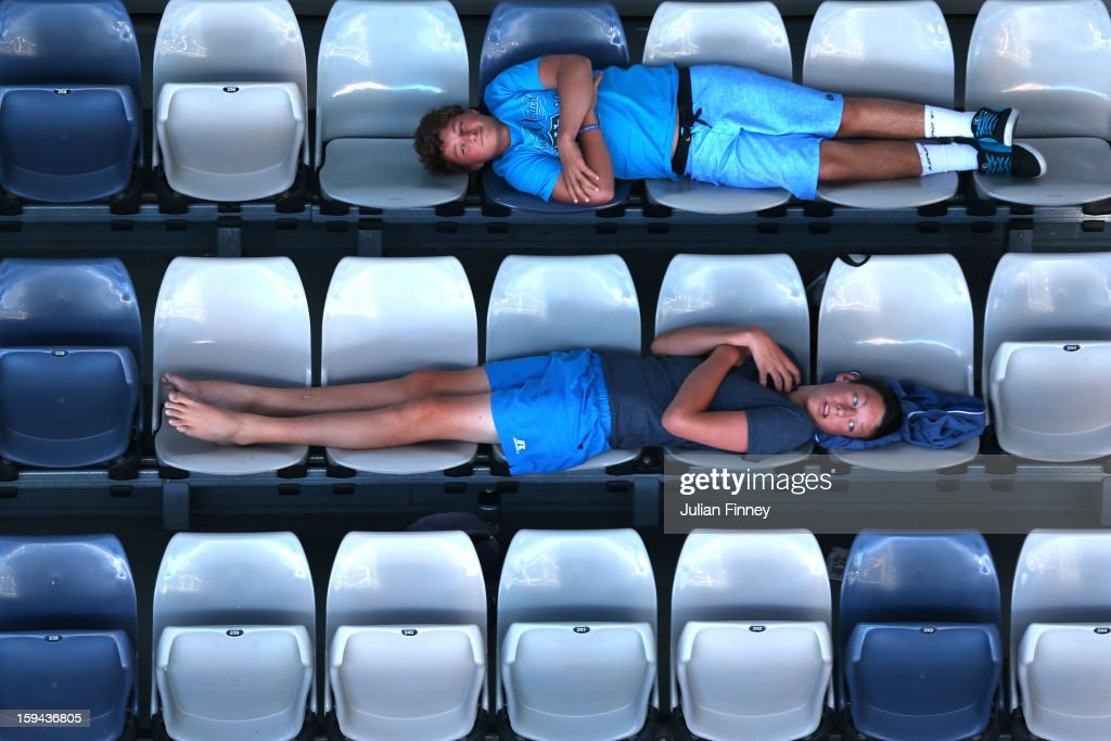 Fans lie across seats in the stands to watch the men's first round match between David Goffin of Belgium and Fernando Verdasco of Spain during day one of the 2013 Australian Open at Melbourne Park on January 14, 2013 in Melbourne, Australia.
