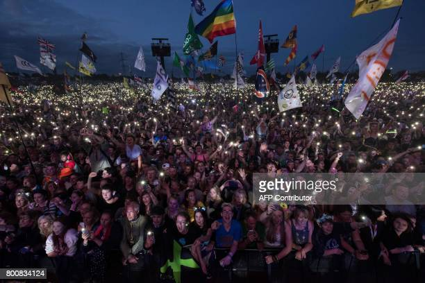 Fans listen as Ed Sheeran performs on the Pyramid Stage at the Glastonbury Festival of Music and Performing Arts on Worthy Farm near the village of...