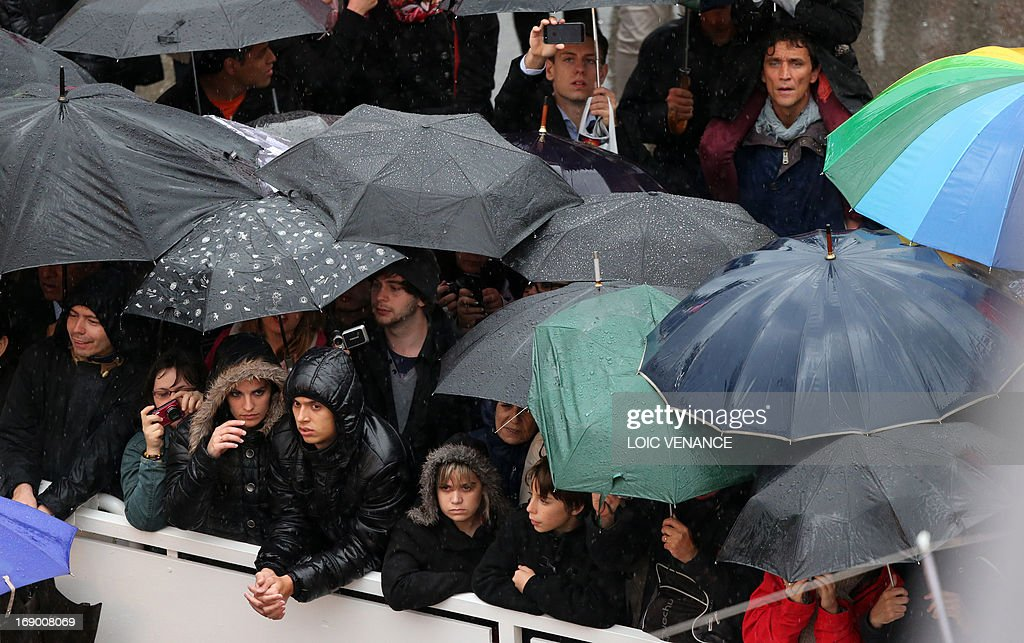Fans look at people walking on the red carpet under pouring rain on May 18, 2013 before the screening of the film 'Jimmy P. Psychotherapy of a Plains Indian' presented in Competition at the 66th edition of the Cannes Film Festival in Cannes. Cannes, one of the world's top film festivals, opened on May 15 and will climax on May 26 with awards selected by a jury headed this year by Hollywood legend Steven Spielberg.