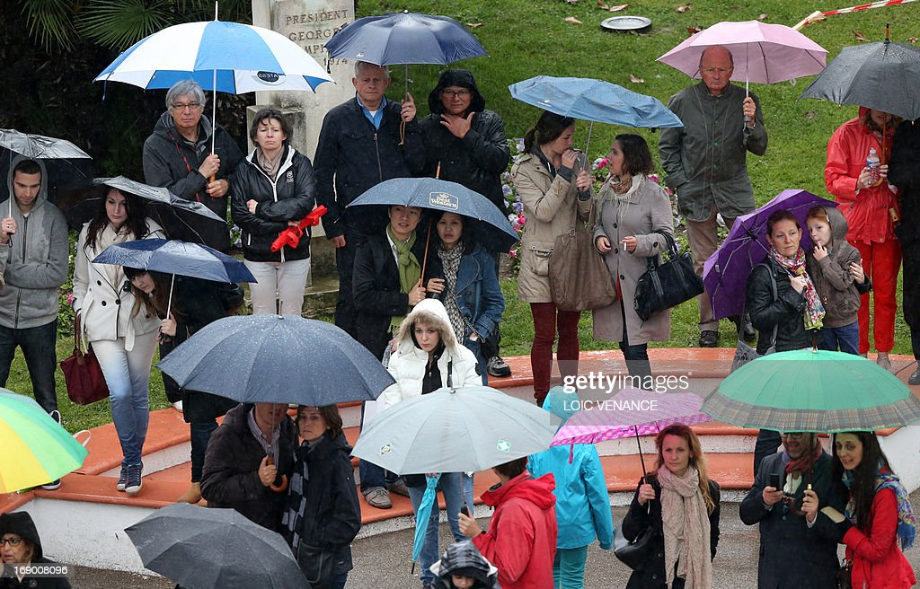 Fans look at people walking on the red carpet under pouring rain on May 18, 2013 before the screening of the film 'Jimmy P. Psychotherapy of a Plains Indian' presented in Competition at the 66th edition of the Cannes Film Festival in Cannes. Cannes, one of the world's top film festivals, opened on May 15 and will climax on May 26 with awards selected by a jury headed this year by Hollywood legend Steven Spielberg. AFP PHOTO / LOIC VENANCE