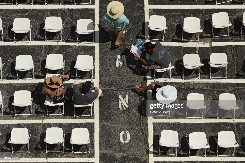 Fans look at racing forms in the grandstand prior to the 93rd running of the Black Eyed Susan Stakes at Pimlico Race Course on May 19, 2017 in Baltimore, Maryland.