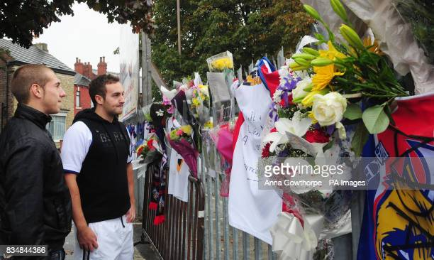 Fans look at tributes that have been left on the gates of Belle Vue in Wakefield the home ground of Wakefield Trinity Wildcats in memory of player...