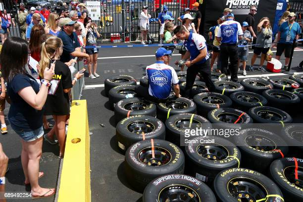 Fans look on as crew members of the Lowe's Chevrolet work before the Monster Energy NASCAR Cup Series CocaCola 600 at Charlotte Motor Speedway on May...