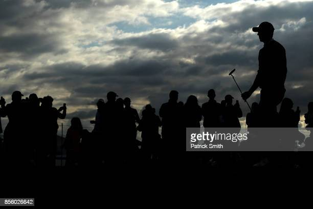 Fans look on as Jordan Spieth of the United States walks up the 16th fairway during Saturday afternoon fourball matches of the Presidents Cup at...