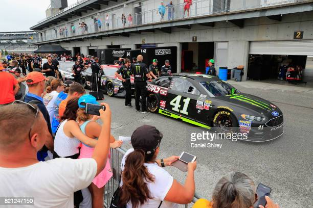 Fans look on as the car of Kurt Busch driver of the Ford goes through inspection prior to the Monster Energy NASCAR Cup Series Brickyard 400 at...
