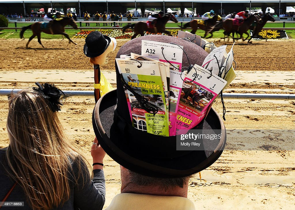 Fans look on as the field races past during the first race prior to the 139th running of the Preakness Stakes at Pimlico Race Course on May 17 2014...