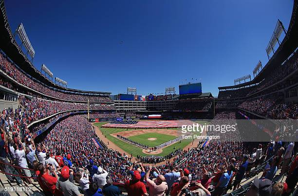 Fans look on as two fighter jets fly over during the National Anthem on Opening Day before the Texas Rangers take on the Seattle Mariners at Globe...