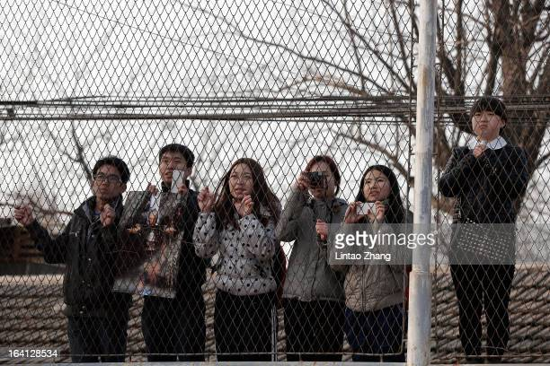 Fans look on standing behind barbed wire during the British football player David Beckham visit to a middle school in Beijing on March 20 2013 in...