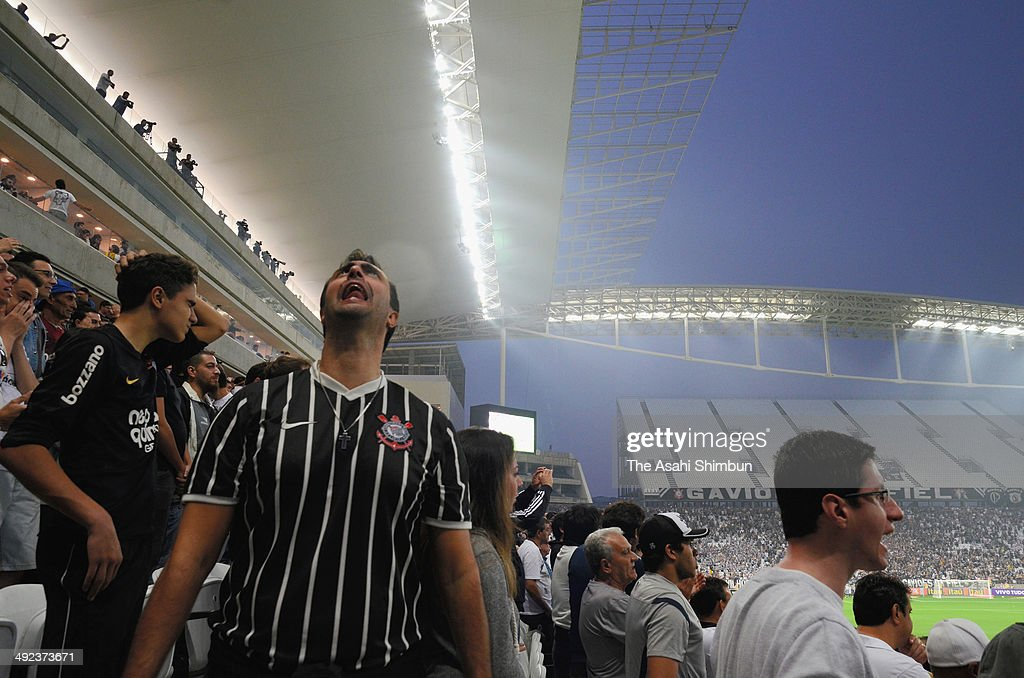 Fans look up raining sky as the construction of the roof of the stadium have not been completed during the Brazilian Series A 2014 match between Corinthians and Figueirense at Arena Corinthians on May 18, 2014 in Sao Paulo, Brazil. The stadium will be used during the World Cup starting next month as Arena de Sao Paulo, hosts the opening game between Brazil and Croatia.