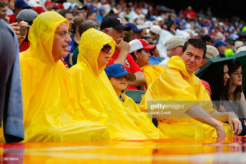 Fans looks on in the rain during a baseball game between the Texas Rangers and the Los Angeles Angels of Anaheim at Rangers Ballpark in Arlington on September 28, 2013 in Arlington, Texas.