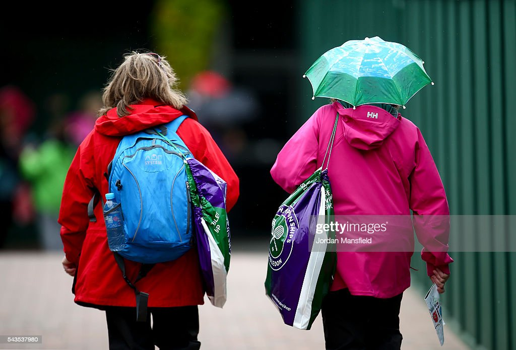 Fans make their way to shelter as rain delays play during day three of the Wimbledon Lawn Tennis Championships at the All England Lawn Tennis and Croquet Club on June 29, 2016 in London, England.