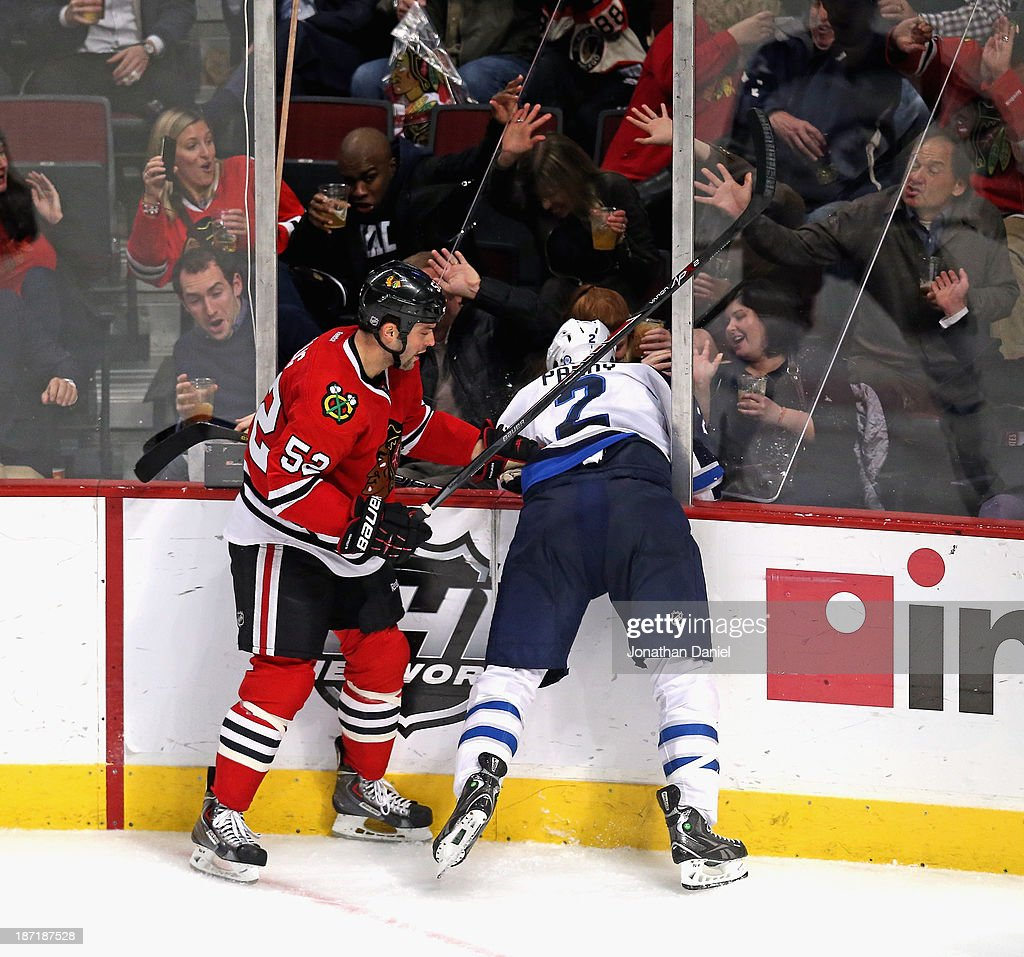 Fans move to hold up the glass after <a gi-track='captionPersonalityLinkClicked' href=/galleries/search?phrase=Brandon+Bollig&family=editorial&specificpeople=7186858 ng-click='$event.stopPropagation()'>Brandon Bollig</a> #52 of the Chicago Blackhawks cehcked <a gi-track='captionPersonalityLinkClicked' href=/galleries/search?phrase=Adam+Pardy&family=editorial&specificpeople=2221762 ng-click='$event.stopPropagation()'>Adam Pardy</a> #2 of the Winnipeg Jets trhough it at the United Center on November 6, 2013 in Chicago, Illinois. The Blackhawks defeated the Jets 4-1.
