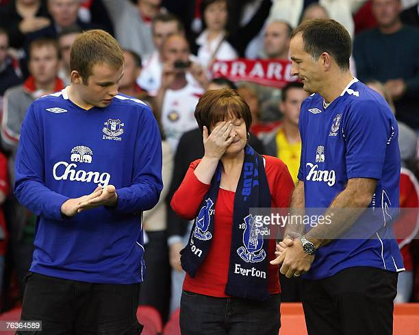 Fans observe a minutes applause for mudered young Everton fan Rhys Jones as his parents Stephen and Melanie and their son Owen look on prior to the...