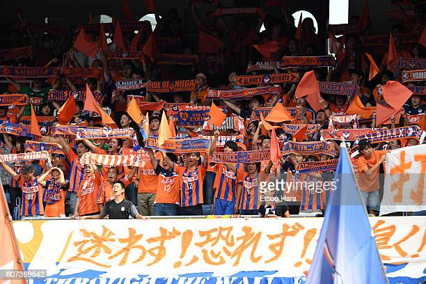 Fans of Albirex Niigata cheer during the JLeague match between Yokohama FMarinos and Albirex Niigata at the Nissan Stadium on September 17 2016 in...